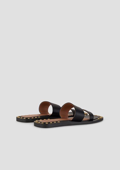 Flat sandals in leather with two straps and golden studs