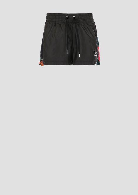 Shorts in tessuto tecnico windproof con retro a fantasia tropicale